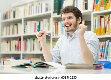 Young handsome male student studying at the table in college library laughing happily shaking his fists in victory gesture copyspace smart success achievement scholarship education exams passing