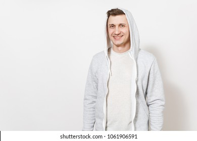 Young handsome male student in t-shirt, blue jeans and light sweatshirt with hood rejoices and smiling in the studio on white background. Concept of emotions, good mood. Copy space for advertisement