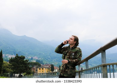 Young handsome male tourist wearing camouflage jacket speaking by smartphone near banister, lake Como and Alps mountain in background. Concept of tourism, modern technology.