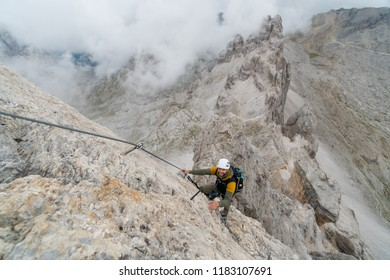 young handsome male university student on a steep and exposed rock face climbs a Via Ferrata in Alta Badia in the South Tyrol
