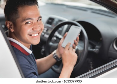young handsome male using mobile phone while driving his car