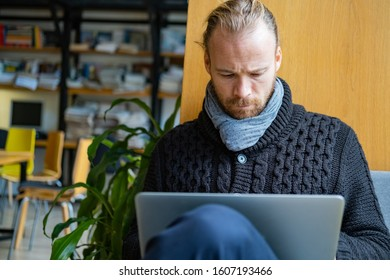 Young handsome male work with computer in library, man with laptop indoors use internet