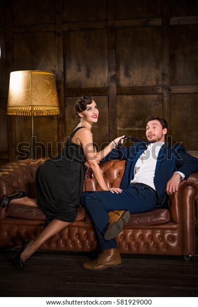 Young handsome man accompanied by elegant lady. Gorgeous lady with red lips having dream to marry rich man. Restaurant atmosphere.