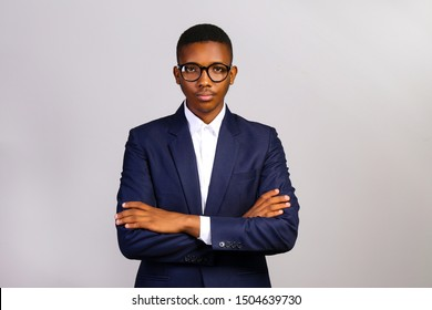 Young handsome man of african american ethnicity wearing classic blue posing over isolated grey background. Portrait of stylish confident male in formal wear. Close up, copy space.