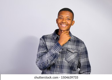 Young handsome man of african american ethnicity wearing checkered shirt posing over isolated background. Portrait of stylish confident male in casual outfit. Close up, copy space.