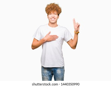 Young handsome man with afro hair wearing casual white t-shirt Swearing with hand on chest and fingers, making a loyalty promise oath