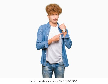 Young handsome man with afro hair wearing denim jacket In hurry pointing to watch time, impatience, upset and angry for deadline delay