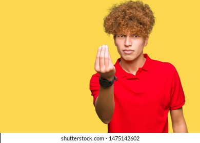 Young handsome man with afro hair wearing red t-shirt Doing Italian gesture with hand and fingers confident expression