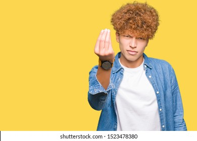 Young handsome man with afro hair wearing denim jacket Doing Italian gesture with hand and fingers confident expression