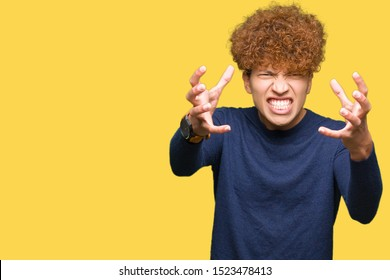 Young handsome man with afro hair Shouting frustrated with rage, hands trying to strangle, yelling mad
