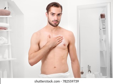 Young handsome man applying cream onto body in bathroom