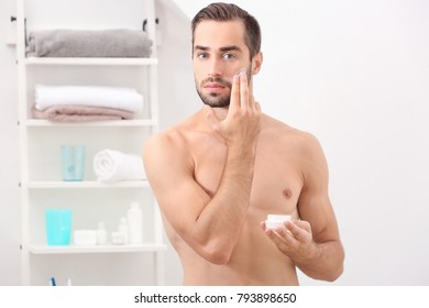 Young handsome man applying cream onto face in bathroom