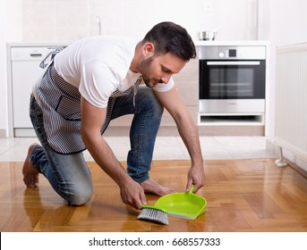 Young handsome man with apron sweeping dust on parquet floor with kitchen in background. Male doing chores. House cleaning service