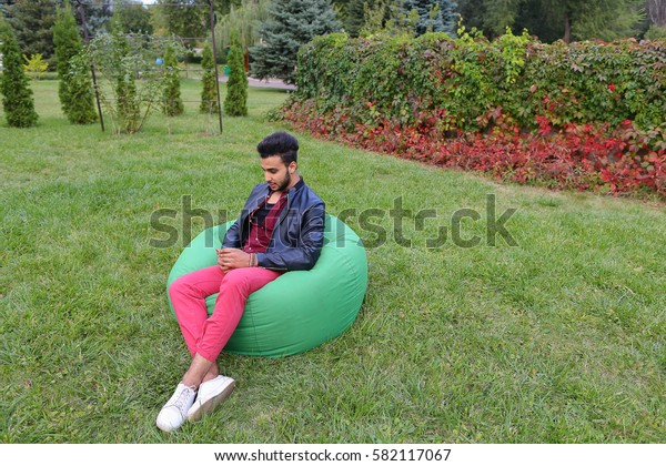Young Handsome Man Arab Businessman, Student Holding Mobile Phone, Gadget and Calls, Communicates on Skype For Video Calling, Smiling and Sitting in Comfortable Green Chair in Garden Outdoors. Bearded