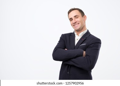 Young handsome man with arms crossed. Cheerful guy laughing and looking at camera with a big grin.