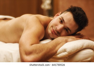 Young handsome man with athletic body lying on massage table at the spa center smiling to the camera copyspace relaxing relaxation leisure resort hotel service pampering body care recreation wellness