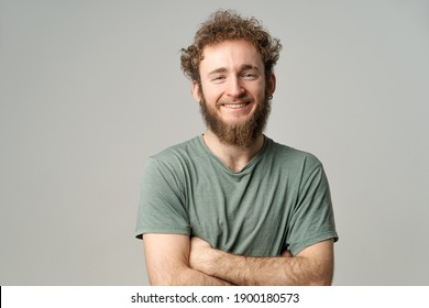 Young handsome man with beard and curly hair in olive t-shirt looking at camera isolated on white background. Portrait of smiling young man with hands folded.