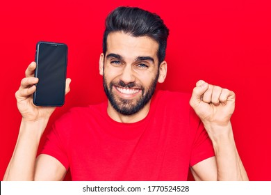 Young handsome man with beard holding smartphone showing screen screaming proud, celebrating victory and success very excited with raised arm