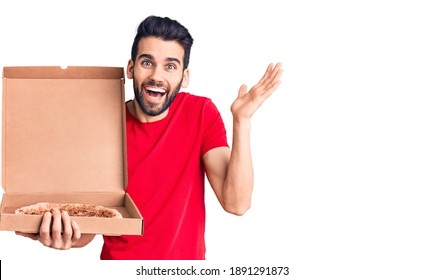 Young handsome man with beard holding delivery cardoboard with italian pizza celebrating victory with happy smile and winner expression with raised hands