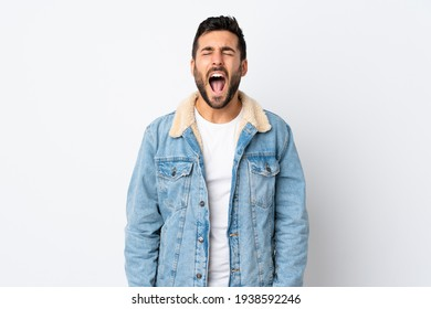 Young handsome man with beard isolated on white background shouting to the front with mouth wide open