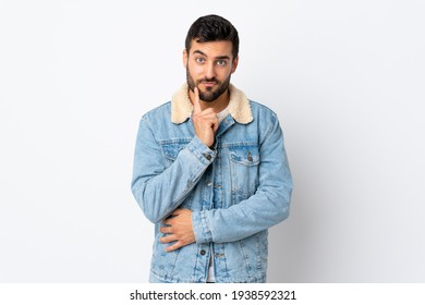 Young handsome man with beard isolated on white background and thinking