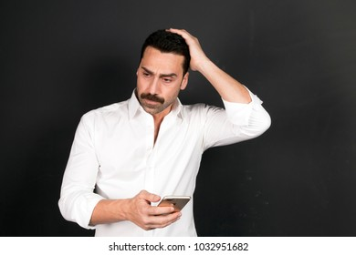 Young handsome man with beard and mustache using a mobile phone with a negative attitude, studio portrait