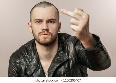 Young handsome man with beard and mustache showing fuck off. hand gesture concept. fuck off. go fuck. bad gesture
