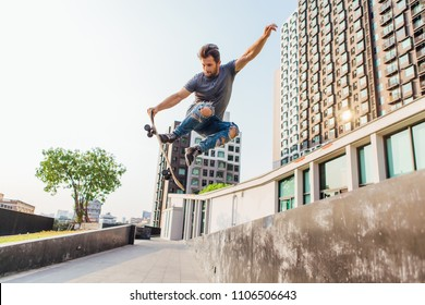 Young handsome man with beard on a skateboard jumping high and making trick