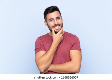 Young handsome man with beard over isolated blue background smiling