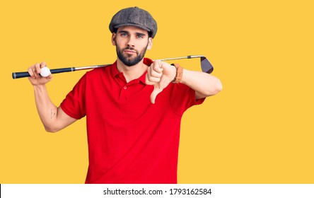 Young handsome man with beard playing golf holding club and ball with angry face, negative sign showing dislike with thumbs down, rejection concept