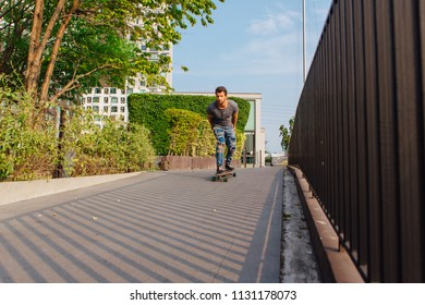 Young handsome man with beard riding longboard on the street.