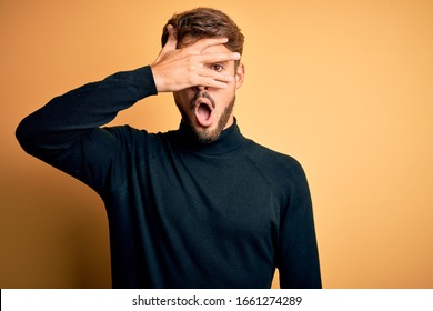 Young handsome man with beard wearing turtleneck sweater standing over yellow background peeking in shock covering face and eyes with hand, looking through fingers with embarrassed expression.