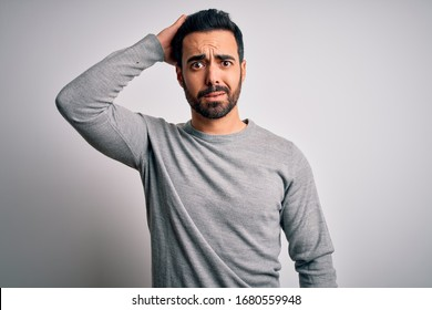 Young handsome man with beard wearing casual sweater standing over white background confuse and wonder about question. Uncertain with doubt, thinking with hand on head. Pensive concept.
