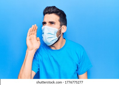 Young handsome man with beard wearing medical mask shouting and screaming loud to side with hand on mouth. communication concept.