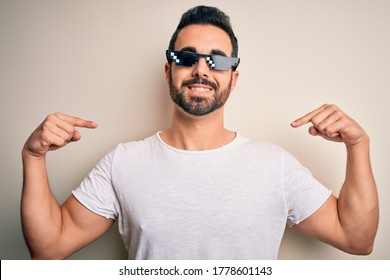 Young handsome man with beard wearing funny thug life sunglasses over white background looking confident with smile on face, pointing oneself with fingers proud and happy.