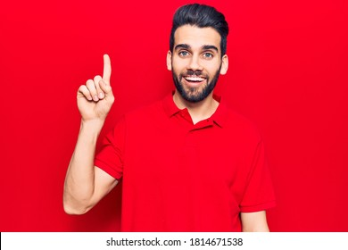 Young handsome man with beard wearing casual polo smiling with an idea or question pointing finger up with happy face, number one