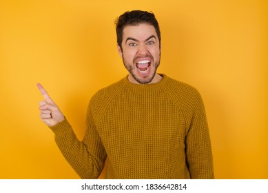 Young handsome man with beard wearing casual sweater over yellow background points aside on copy blank space. People promotion and advertising concept