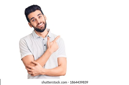 Young handsome man with beard wearing casual polo with a big smile on face, pointing with hand and finger to the side looking at the camera.