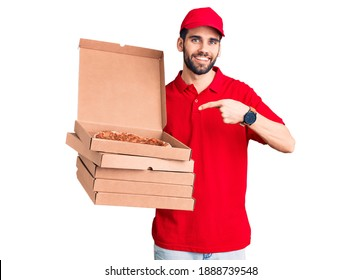 Young handsome man with beard wearing delivery uniform holding boxes with pizza smiling happy pointing with hand and finger