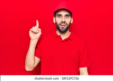 Young handsome man with beard wearing casual polo and cap smiling with an idea or question pointing finger up with happy face, number one