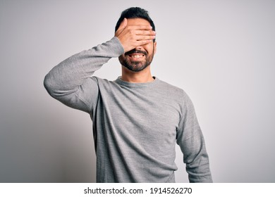 Young handsome man with beard wearing casual sweater standing over white background smiling and laughing with hand on face covering eyes for surprise. Blind concept.
