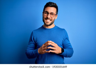 Young handsome man with beard wearing casual sweater and glasses over blue background Hands together and fingers crossed smiling relaxed and cheerful. Success and optimistic