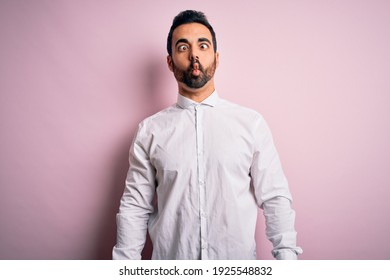 Young handsome man with beard wearing casual shirt standing over pink background making fish face with lips, crazy and comical gesture. Funny expression.