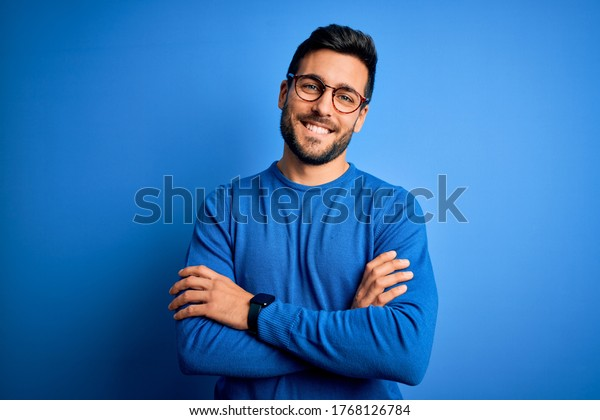 Young handsome man with beard wearing casual sweater and glasses over blue background happy face smiling with crossed arms looking at the camera. Positive person.