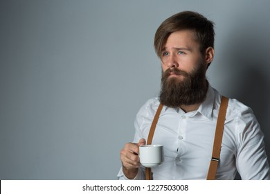 Young handsome man with a beard in a white shirt and yellow suspenders with cup coffee or tea on a gray background
