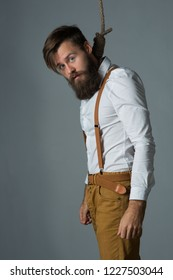 Young handsome man with a beard in a white shirt and yellow suspenders on gallows on a gray background