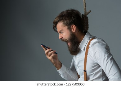 Young handsome man with a beard in a white shirt and yellow suspenders talk to phone on gallows on a gray background