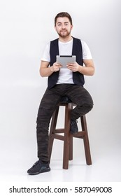 young handsome man with beard in white shirt and black waistcoat holding tablet and sits on chair on gray background
