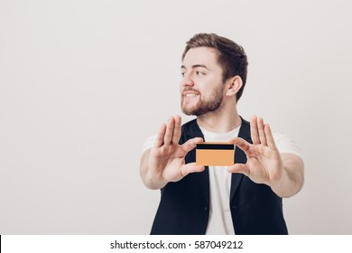 young handsome man with beard in white shirt and black waistcoat holding plastic credit card and smiling. focus on card. soft light