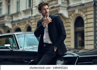 Junge gut aussehende Mann mit schwarzem Oldtimer mit schwarzem Anzug